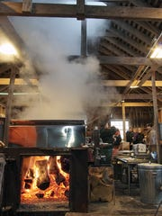 Stearm rises from the sugar house as an employee talks