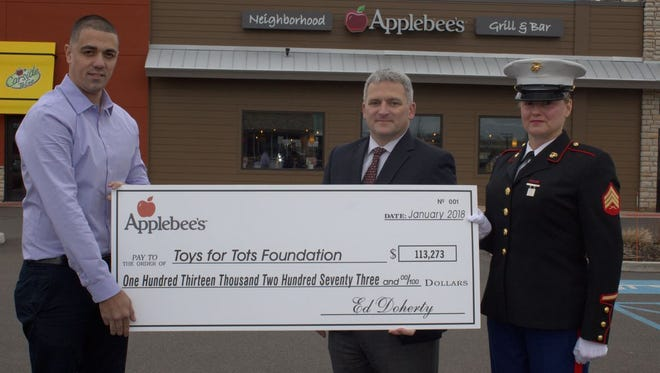 Shimon Peretz, general manager, Applebee's of Clark; Col. Ted Silvester, United States Marine Corps (Ret.) and vice president of marketing and development, Toys for Tots; and Staff Sgt. Stacey Van Liera, United States Marine Corps participate in the check presentation.