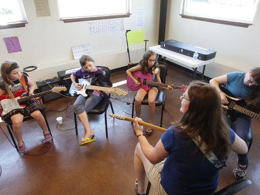 Natalie Wlodarczyk gives a guitar lesson to Calli Howe (from left), Anisa Peterson, Gracie Daniels and Natalie Stacey at Queen City Rock Camp on Wednesday, July 9, 2014.