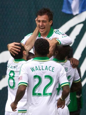 Maximiliano Urruti, top, celebrates his first career MLS goal.