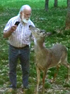 Charles Patterson stands with the deer that has started visiting his property in Robertson County.