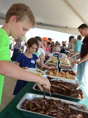 Trenton Stejska, 9, shows how to load up a plate of food.