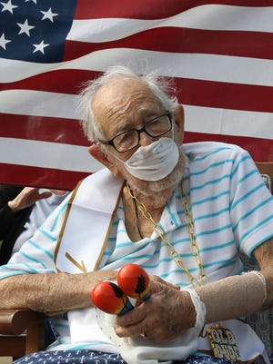 Tony Ulrich sits with Brookfield Assisted Living residents, Saturday, July 18, 2020, helping him celebrate his100th birthday as a parade of well wishers, family and friends passes by.