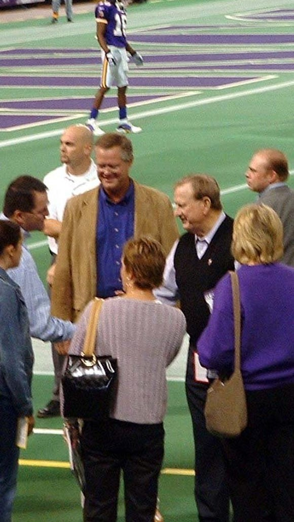 Kelby Krabbenhoft (in tan jacket) meets with Vikings owner Red McCombs  (in dark vest) on the Metrodome field before a game in 2003.