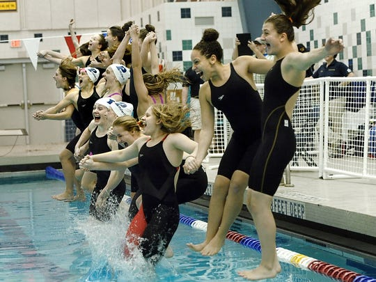Pittsford swimmers celebrate their sectional championship, the schools' 13th straight win, following the 2014 Section V Class A meet at the Webster Aquatic Center.