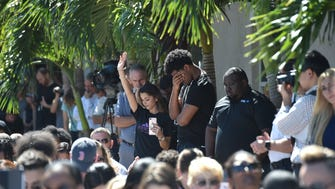 Students bow their heads in prayer along with the crowd during the community prayer vigil for Marjory Stoneman Douglas High School shooting victims on Thursday, Feb. 15 at Parkridge Church in Coral Springs.