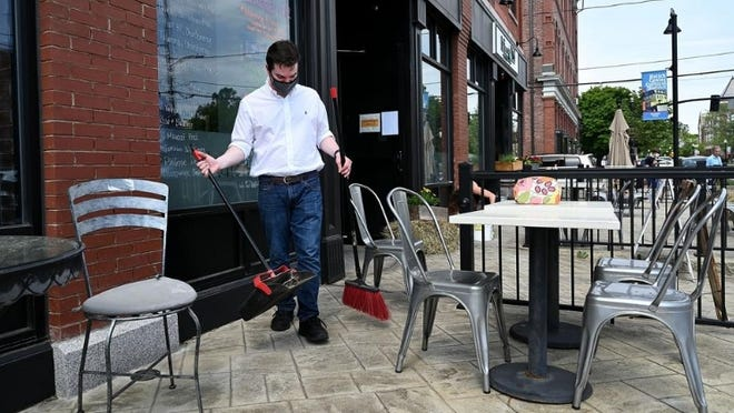 A server at Buttercup in Natick sweeps the patio outside the West Central Street eatery.