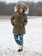 Tiffani Mitchell wears a Fabletics workout outfit and Canada Goose Rossclair parka in olive green with coyote trim and structured hood.