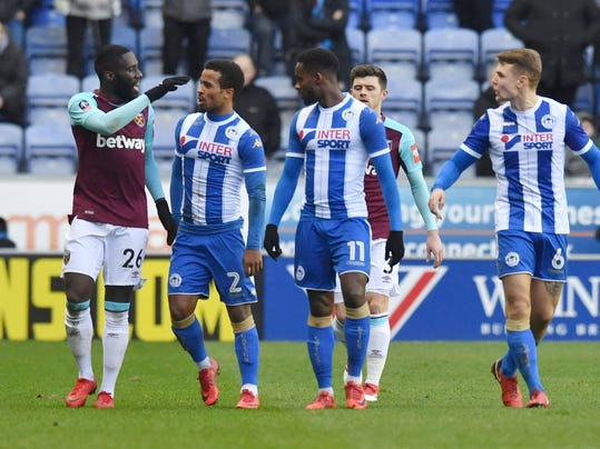 West Ham United's Arthur Masuaku, left, leaves the field after being sent-off during the FA Cup, fourth round match against Wigan at the DW Stadium, Wigan, England, Saturday Jan. 27, 2018. Arthur Masuaku apologized Sunday for spitting at opponent during West Ham's FA Cup defeat to Wigan. The defender was sent off during the Hammers' 2-0 defeat to third-tier Wigan on Saturday as he reacted to a challenge from Nick Powell. (Anthony Devlin/PA via AP)