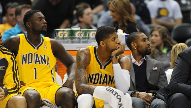 Indiana Pacers Lance Stephenson, Paul George and C.J. Watson look rather glum as they watch fourth quarter action as the San Antonio Spurs beat the Indiana Pacers 103-77 at Bankers Life Fieldhouse March 31, 2014.
