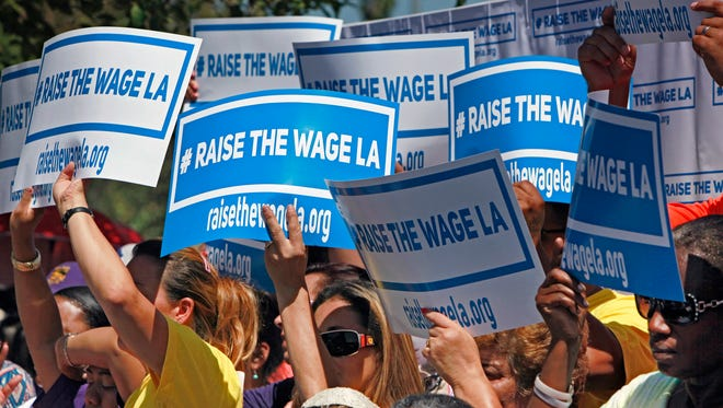 Supporters carry signs to raise the minimum wage in Los Angeles as they listen to Mayor Eric Garcetti during an announcement at  the Martin Luther King, Jr. Park with a coalition of business, labor, community, and faith leaders from across the city on Monday, Sept. 1, 2014.