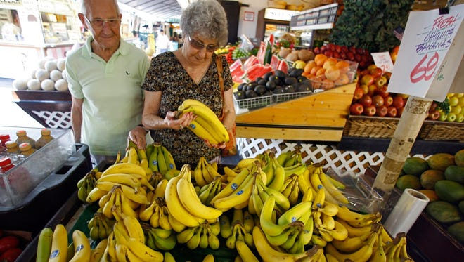 Customers shop for Chiquita bananas at a produce stand at the Farmers Market in Los Angeles.