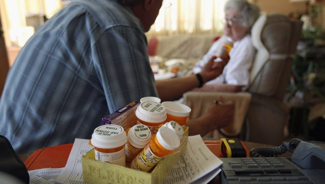 Registered nurse Steve Van Dyke checks patient Mildred Herman's medication while on a home health care visit on March 23, 2012 in Denver, Colo.