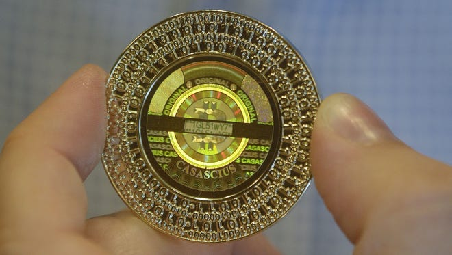 Software engineer Mike Caldwell holds a 25 Bitcoin token at his shop in Sandy, Utah.