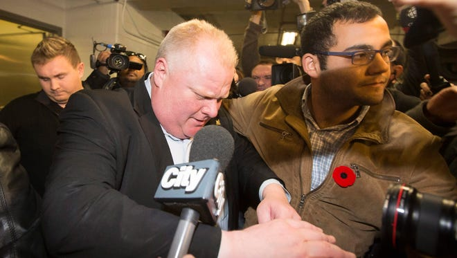 Toronto Mayor Rob Ford walks to his car through a pack of reporters and camera operators in the parking garage after talking on his weekly radio show in Toronto on Sunday.