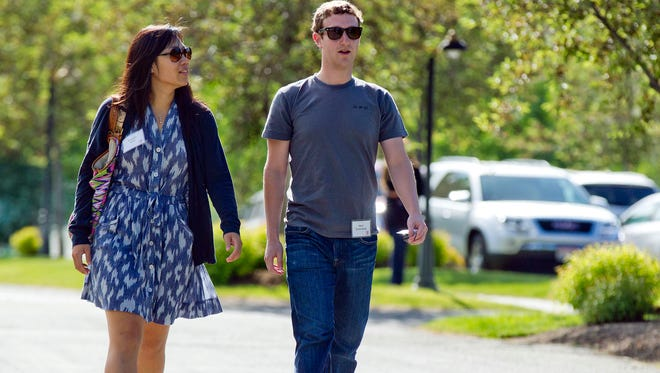 Mark Zuckerberg, president and CEO of Facebook, walks with Priscilla Chan during the 2011 Allen and Co. Sun Valley Conference, in Sun Valley, Idaho.