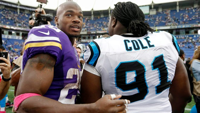 Minnesota Vikings running back Adrian Peterson (left) meets with Carolina Panthers defensive tackle Colin Cole after a loss to the Panthers.