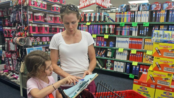 Colleen Liberatore of Eastchester goes over the school supply list with her daughter Katie, 8, while they do their back to school shopping at Value Drug in Eastchester on Wednesday. Katie will be a third-grader at the Anne Hutchinson School in Eastchester.