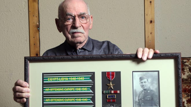 Michael Barone of Northern Kentucky holds a display of memorabilia from his service in World War II. Barone was a member of the 316th Troop Carrier, 44th Squadron, working on aircraft and transporting fuel. He was awarded the Bronze Star.