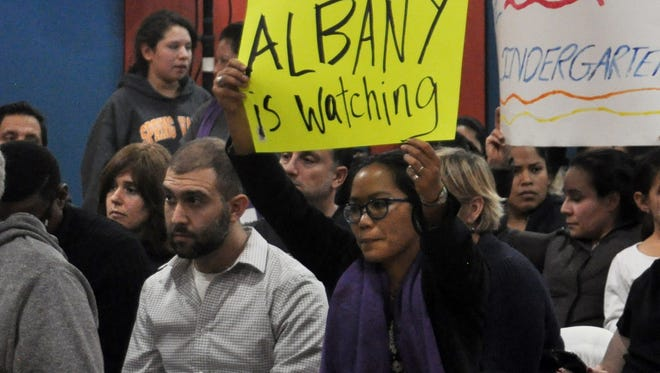 Andrew Mandel, second from left, and Julie Guerrero, holding sign, join Latino community protesters Tuesday at an East Ramapo school board meeting.