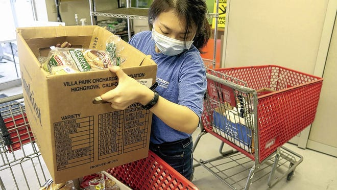 Volunteer Lulu Li loads food packages into a cart for home deliveries Sept. 17 at the Worthington Resource Pantry. The pantry has been hit hard by the COVID-19 coronavirus pandemic and is asking supporters to participate in a virtual 5K fundraiser.