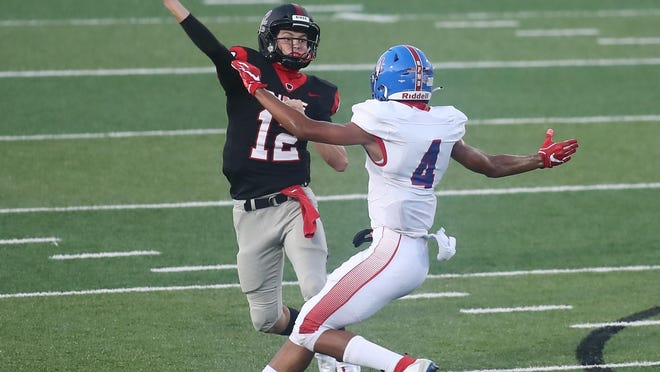 Vista Ridge quarterback Kyle Brown, left, evades Hays defender Michael Boudoin in the first quarter of a nondistrict football game Sept. 24 at Gupton Stadium. Brown threw for 413 yards and six touchdowns and ran for another score in the Rangers' 63-35 win.