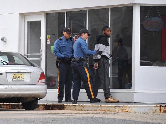 Violent police investigate place a man in handcuffs