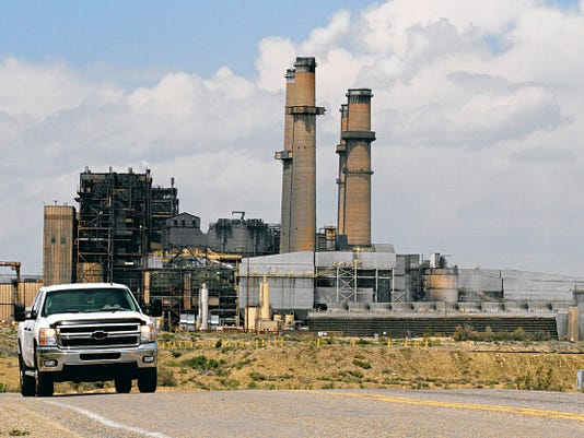 A car on April 20 drives away from the San Juan Generating Station on County Road 6800 in Waterflow.