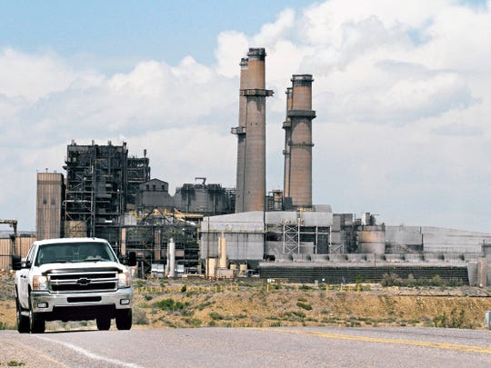 A car drives away from the San Juan Generating Station in April on County Road 6800 in Waterflow in this undated file photo.