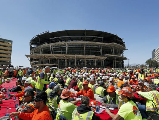 Construction works eat lunch by an MGM arena being built behind the New York-New York casino-hotel in Las Vegas on April 7. The NHL is one step closer to establishing expansion teams in Las Vegas and Quebec City. The league announced Tuesday it has received applications from prospective ownership groups in both markets, a day after a deadline for submissions.