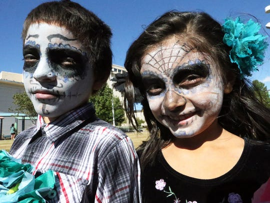 Francisco Lopez, 9, and sister Martha Lopez, 8, sport painted faces done by their mother, Jannette Lopez, on Saturday at the Dia de los Muertos event at Cleveland Square Park in Downtown El Paso.
