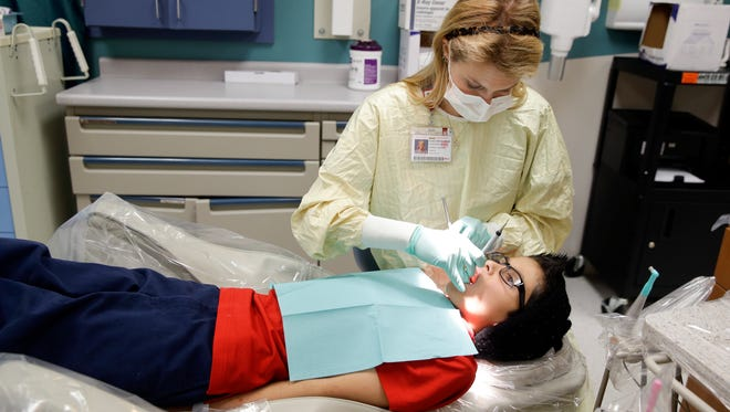 Dental resident Madison Myers Galloway checks the teeth of Justin Perez, 11, during an office visit Jan. 22, 2016, at Riley Hospital for Children's Department of Pediatric Dentistry in Indianapolis. A federal report says three out of four children did not receive all required dental services, such as regular checkups and fluoride treatments, in Medicaid programs in four states. One in four kids failed to see a dentist at all.