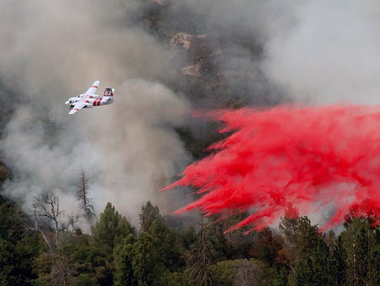 An air tanker drops retardant while fighting to stop