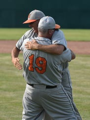 Northville coaches hug after their team beat Rochester