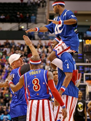 Colts' punter Pat McAfee exchanged high fives with the Harlem Globetrotters after running a play with them Monday at Bankers Life Fieldhouse.
