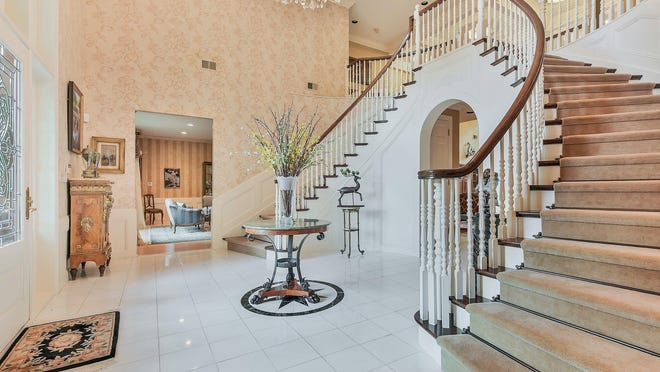 The foyer has marble floors, a crystal chandelier and butterfly stairs to the second-floor landing.