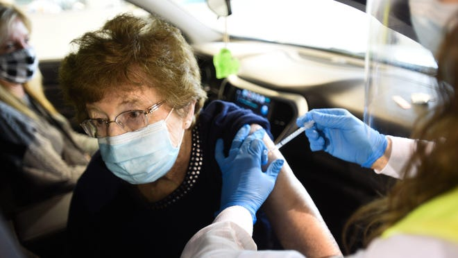 Revella Smith, 95, of Westphalia gets her COVID-19 vaccination Tuesday, Jan. 19, 2021, at the Sparrow Laboratories Drive-Thru Services site at Frandor Shopping Center in Lansing, the first day of public vaccinations for those 70 and older, and for frontline essential workers.