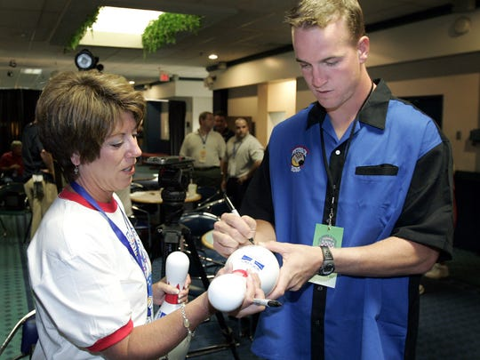 Peyton Manning signs an autograph for Vicki Perry at