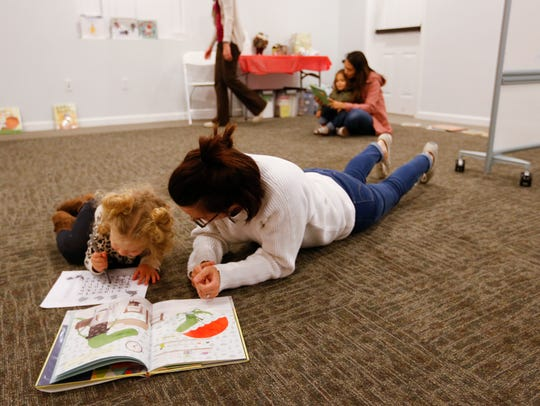 Stashia Casimir reads to her daughter Aveline, 2, during a Ujima program meeting at the Bartley-Decatur Neighborhood Center on Wednesday, Dec. 13, 2017.