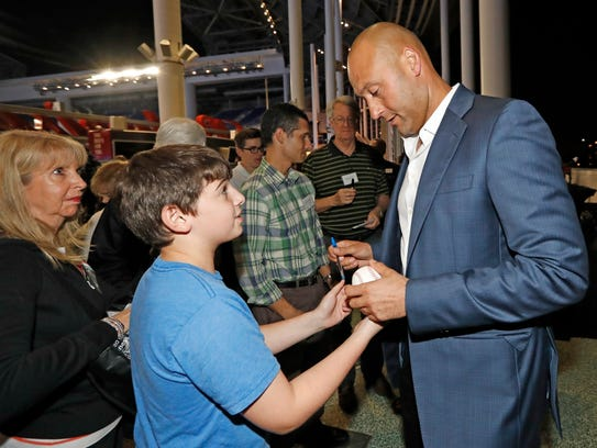 Miami Marlins co-owner Derek Jeter gives an autograph