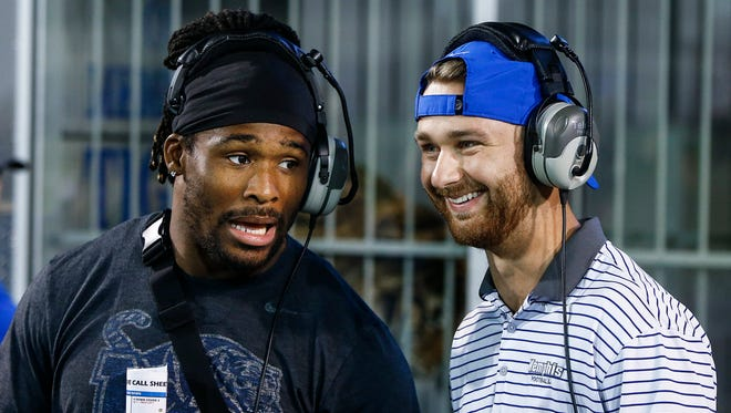 Former Memphis greats DeAngelo Williams (left) and Jake Elliott (right) don headset before taken on their coaching duties during the Tigers spring football game at Liberty Bowl Memorial Stadium.