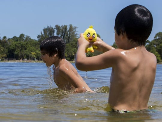Brothers Angelo Victores, 5, and Anthony Victores, 8, play together in Lake Avalon at Sugden Regional Park on June 23, 2016 in Naples, Florida. (Nicole Raucheisen/Staff)