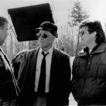 """Writer/producer/director John Hughes (right) discusses a scene with Steve Martin  (center) and John Candy on location in  """"Planes, Trains and Automobiles."""" The movie is an uproarious cross-country comedy about two hilarious mismatched traveling companions experiencing Murphy's Law of American transportation while traveling to Chicago for the Thanksgiving holiday."""