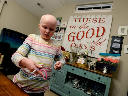 Rose Tavenner, 7, helps her mother Kristi with wrapping Christmas Gifts on Thursday, Dec. 14, 2017, in Nolensville, Tenn. Rose has alopecia, an auto-immune disease that causes hair loss. Mom and daughter now want to help others understand that beauty isn't just on the outside. It is about being bold, brave, confident and compassionate.