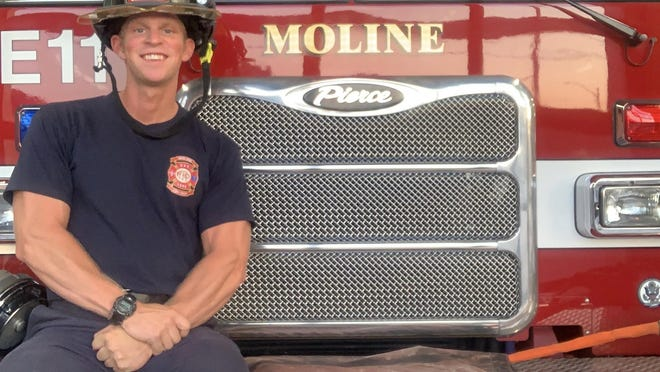 Carson Cheesman poses for a photo recently while sitting on the front of Moline Fire Department engine No. 11.