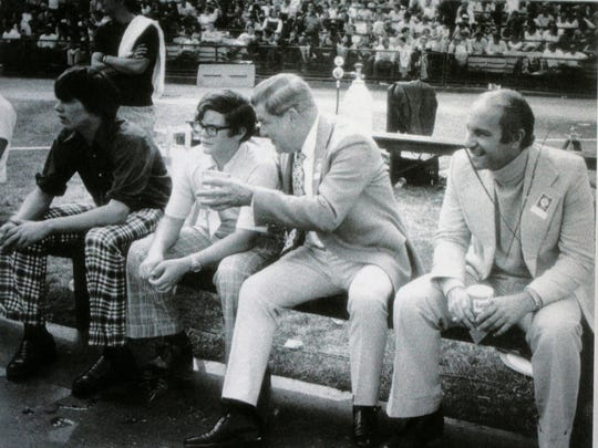 A young Jim Irsay (center) on the sidelines, getting pointers from his father Bob.