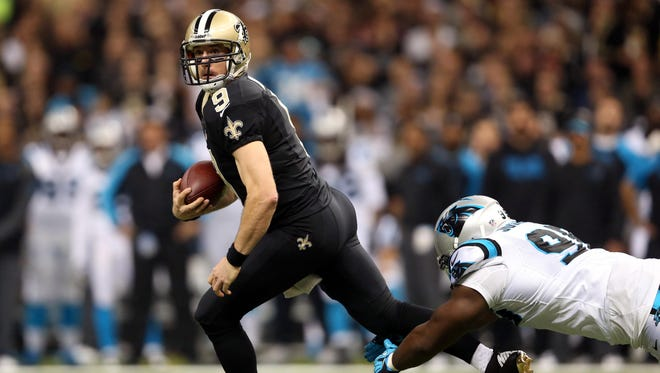 New Orleans Saints quarterback Drew Brees (9) carries the ball before being tripped up by Carolina Panthers defensive end Charles Johnson (95) in the first quarter at the Mercedes-Benz Superdome on Dec. 8, 2013.