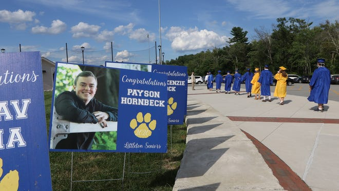The Littleton High School Class of 2020 walks past their signs as they head to Alumni Field Friday evening, July 31, 2020.