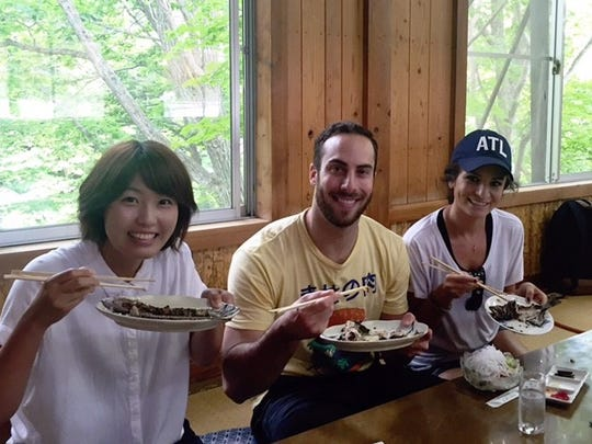 Anthony Bass eats his catch with wife Sydney Rae and a local television host in Japan.