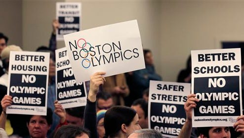 FILE - In this Feb. 5, 2015, file photo, people hold up placards in Boston, against the Olympic Games coming to the city, during the first public forum regarding the city's 2024 Olympic bid. Boston's bid for the 2024 Summer Olympics flamed out in spectacular fashion earlier this week, with local organizers and the U.S. Olympic Committee deciding to part ways after the Boston mayor and the Massachusetts governor refused to be rushed into a decision putting taxpayers on the hook if the games went over budget. (AP Photo/Charles Krupa, File)